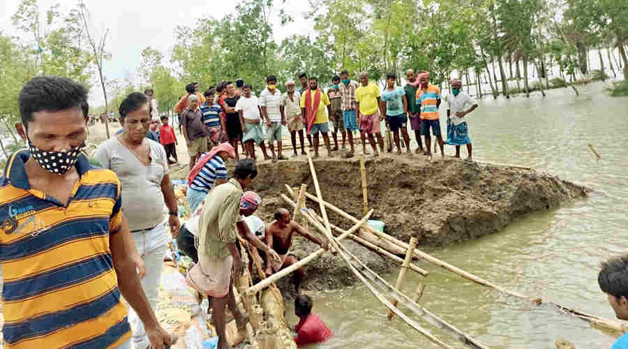 Villagers try to repair a breached embankment at Patharpratima in South 24-Parganas on Thursday, a day after Cyclone Yaas.