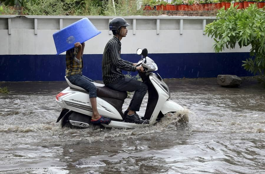 Commuters make their way through a water-logged road after heavy rain in Amritsar on Monday.