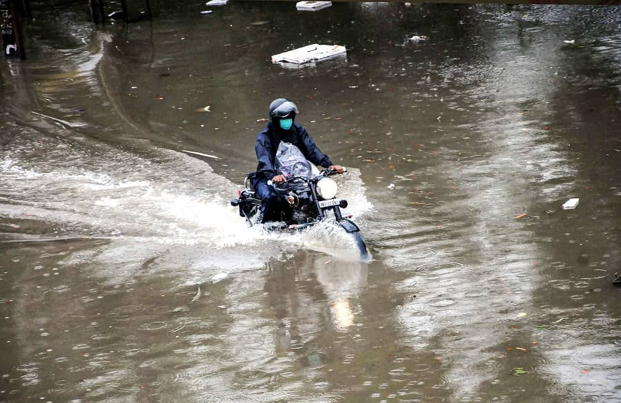 A commuter wades through a waterlogged road at Chandani Chowk in Patiala on Tuesday.