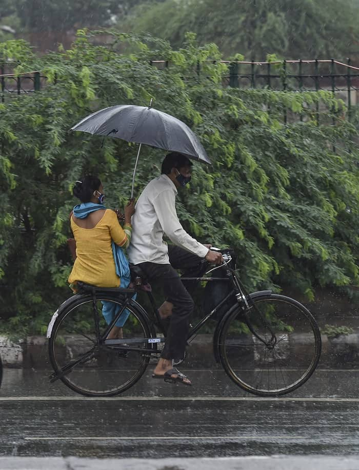 Commuters carry an umbrella during rain as monsoon reaches New Delhi, on Tuesday.