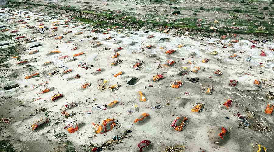 Bodies, some of them believed to be of Covid-19 victims,  are seen partially exposed in shallow sand graves after rain washed away the top layer of sand on the banks of the Ganga in Shringverpur near Allahabad on May 20.