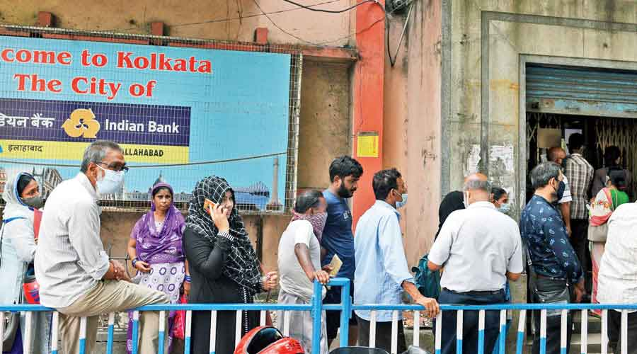 Customers wait outside the Park Circus branch of Indian Bank on Monday.