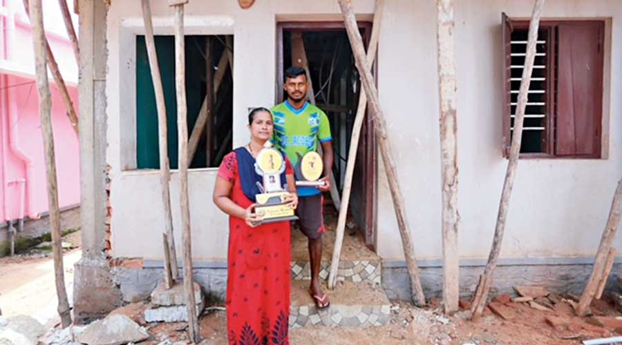 Anil Antony with his mother Sarjin in front of their house.