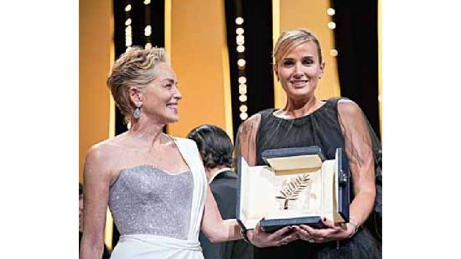Julia Ducournau (right), the winner of the prestigious Palme d'Or for Titane, with actor Sharon Stone, who presented the award