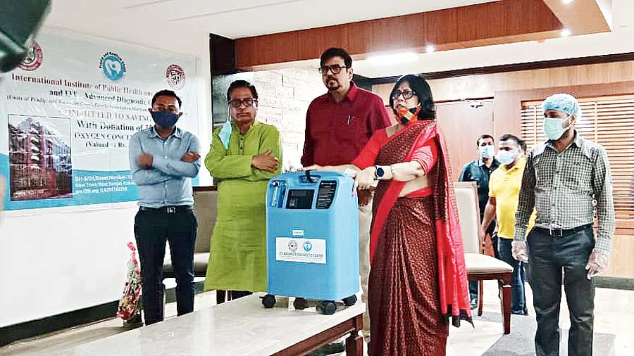 Anuradha Bhowmik, managing administrator of I3TK, handing over one of the oxygen concentrators to Sujit Bose at the New Town premises of the institute. To his right are MLA Aditi Munshi's husband and Bidhannagar Municipal Corporation Board of Administrators member Debraj Chakraborty (extreme left) and MLA Tapash Chatterjee