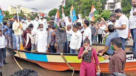 Congress workers protest against water-logging in Bhubaneswar standing on a boat in the Odisha capital on Friday