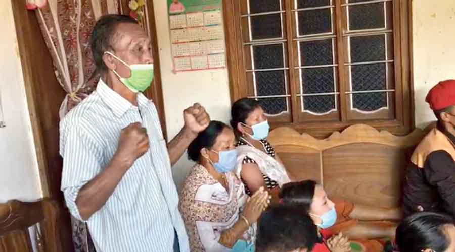 Chanu's father Saikhom Kriti cheers for his daughter as the family  watches her event on television at their home in Imphal East  in Manipur.