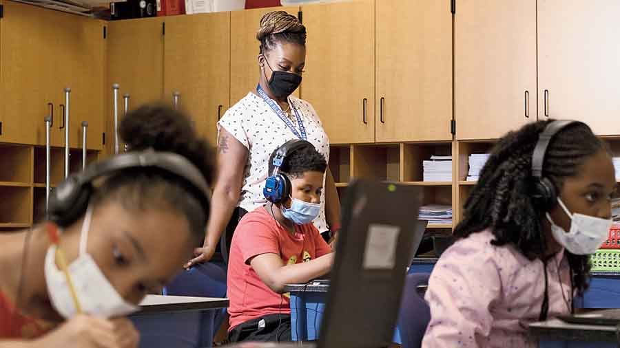 Tonette McQueen helps Zion Graham, 8, with an assignment during a summer school class in Greensboro, North Carolina.