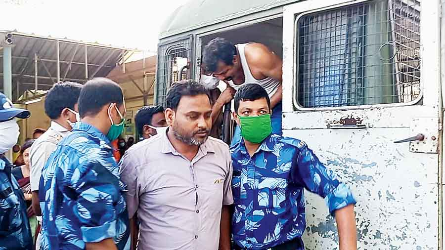 A person arrested for the violence being brought to Raiganj Medical College & Hospital for a medical test on Wednesday.