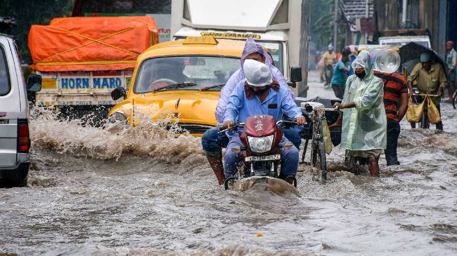 Vehicles wade through a waterlogged road during rain in Howrah on Thursday.