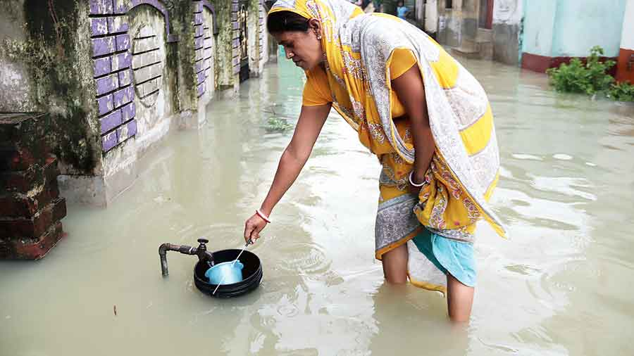 A woman collects water from a tap on a street flooded by the Banka river in Burdwan town on Friday.