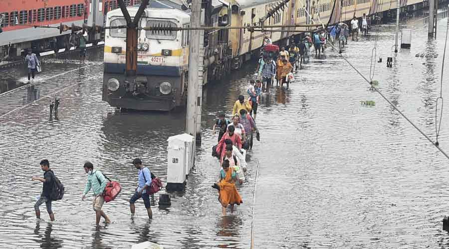 Passengers deboard from a train stuck on a waterlogged area following heavy rains at Tikiapara area in Howrah, on Friday.