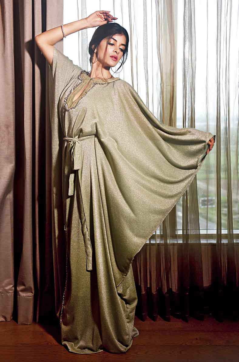 """Keeping up with the monsoon colour palette of blues and greens, Madhumita in this metallic pista green kaftan outfit cuts a relaxed and sensuous frame. The look, perfect for an intimate house party, has sequin detailing,a front slit designed upwards from the hem, a deep-cut neckline with antique gold and silver embroidery adding to the glam. Effortless fish braid, nude lips and natural make-up keep it subtle. """"This outfit is perfect for a glamorous evening affair. The silhouette is soft and fluid and promises timelessness and eternal elegance,"""" says Jyotee."""