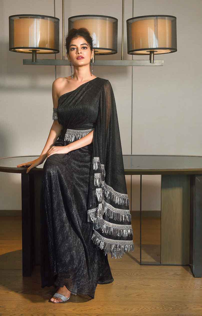 """You can never go wrong in black and bling for a party! Keep the monsoon party look glam and classy yet fuss-free in this metallic black pre-draped sari. Detailed with tassel embellishments, this one-shoulder outfit has metallic straps around the waist and on one arm, accessorising the look. The lips are highlighted in a contrast maroon and the hair is tied up into a messy bun, complementing the one-shoulder style. """"Black with bling has its own fan base! Classy and stylish, this outfit allows you to bare some skin in the one-shoulder wondrous sensuous drape, making one feel like a diva,"""" says the designer."""