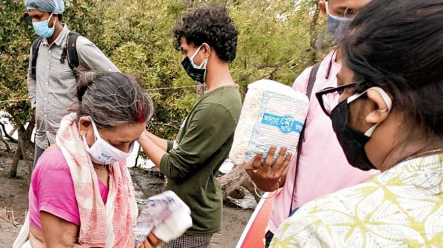 An elderly woman keeps a water pouch in a bag after receiving it from a relief team on remote Bholakhali island on Monday.