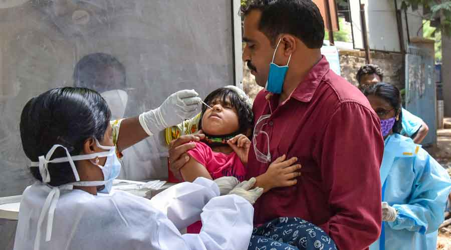 A health worker collects swab sample of a child for Covid-19 test, at Urban Health Centre in Musharabad