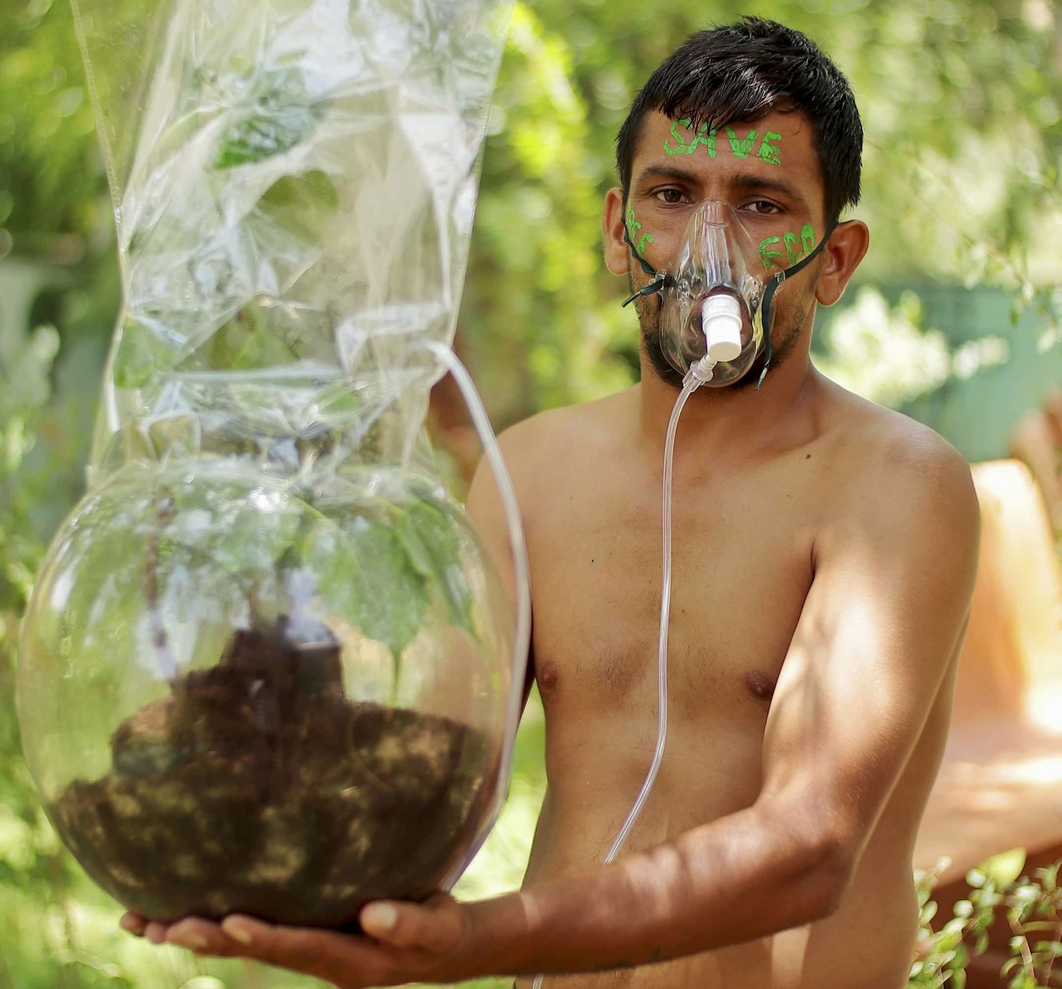 A man poses with a plant connected with an oxygen mask in Barmer on the occasion of World Environment Day on Saturday.