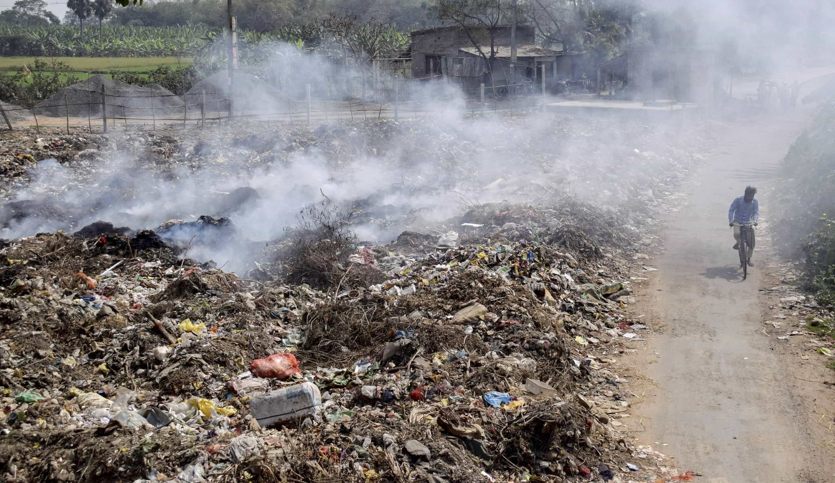 A man on a cycle passes through a dumping ground in Nadia as smoke billows from the garbage on Saturday.