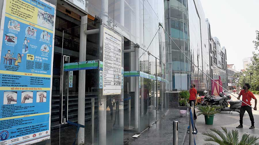 A worker sprays disinfectant to sanitise a mall ahead of its reopening as the unlocking process of the Covid-19 lockdown begins in New Delhi on Sunday.