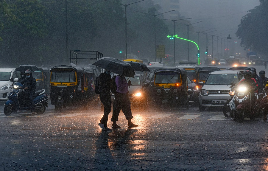Commuters make their way during heavy rain, near Oberoi Mall at Goregaon, in Mumbai on Wednesday.