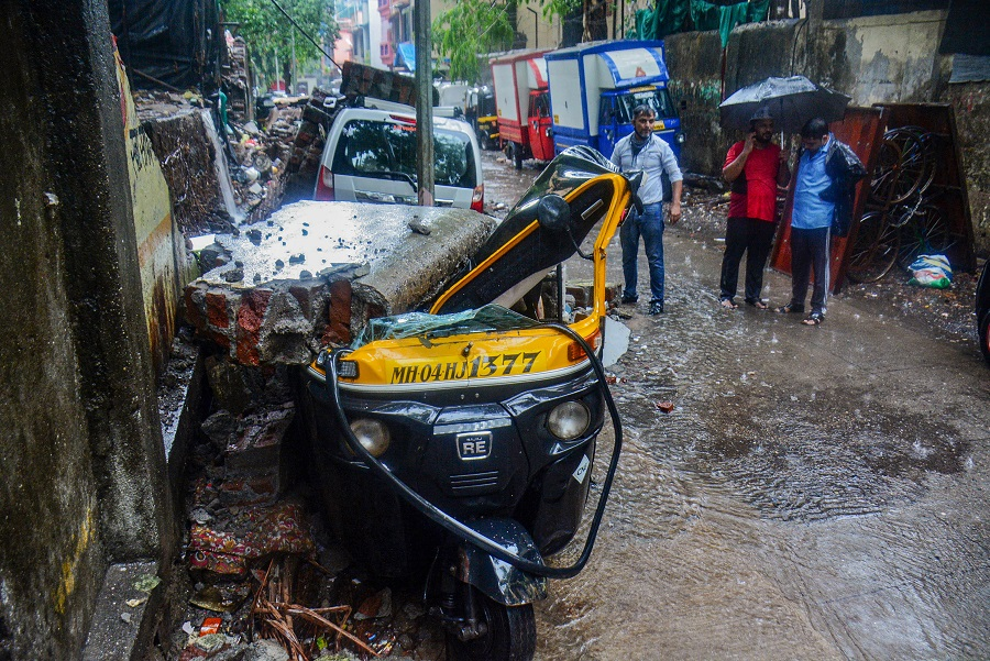 Vehicles damaged after a society compound wall fell on them following heavy rain, at Savarkar Nagar, in Thane on Wednesday.