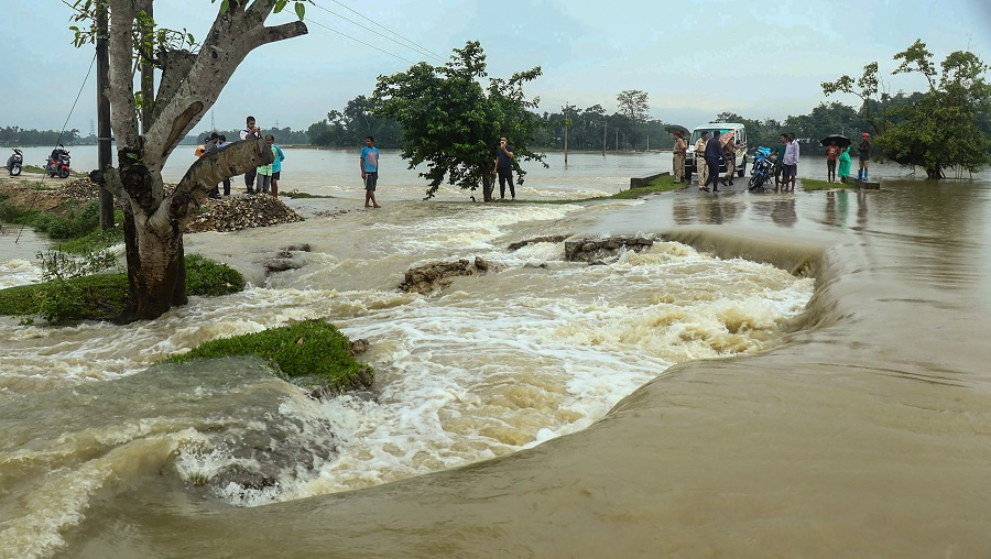 People stand near a waterlogged road after heavy rainfall in Barpathar on Wednesday.