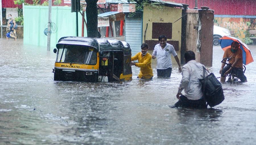 People wade through a waterlogged street near Vandana Cinema Bus Stand, in Thane on Wednesday.