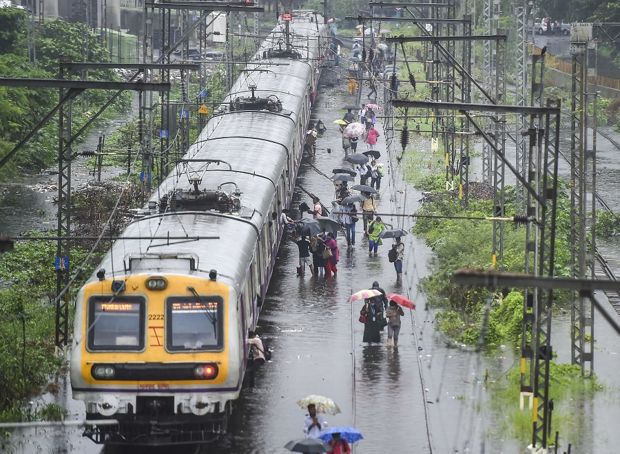 Stranded local train commuters walk on the waterlogged railway tracks during rain, at Kurla, in Mumbai on Wednesday.