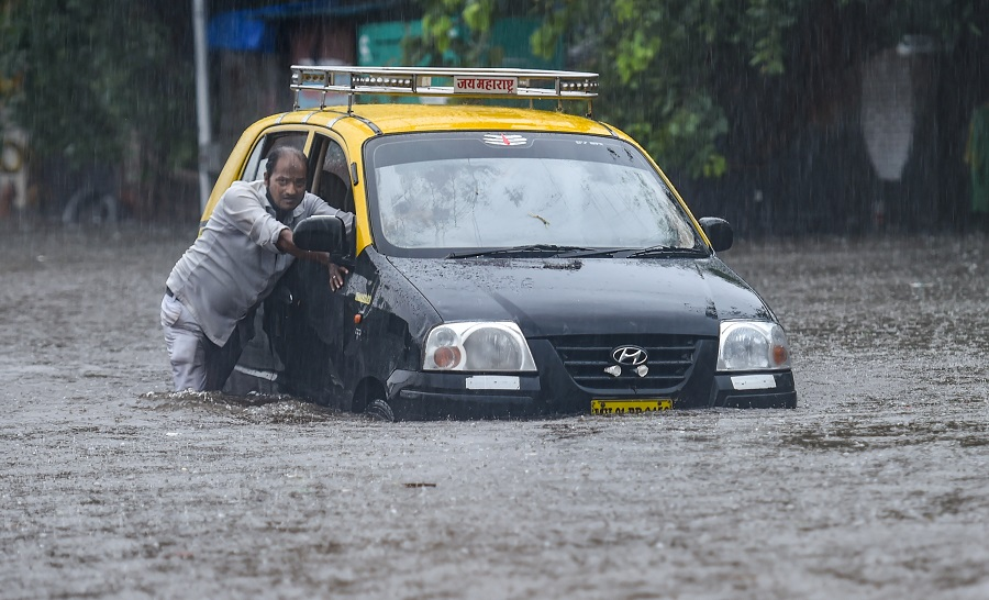 A taxi driver pushes his car as he tries to wade through a waterlogged street at Hindmata in Mumbai on Wednesday.