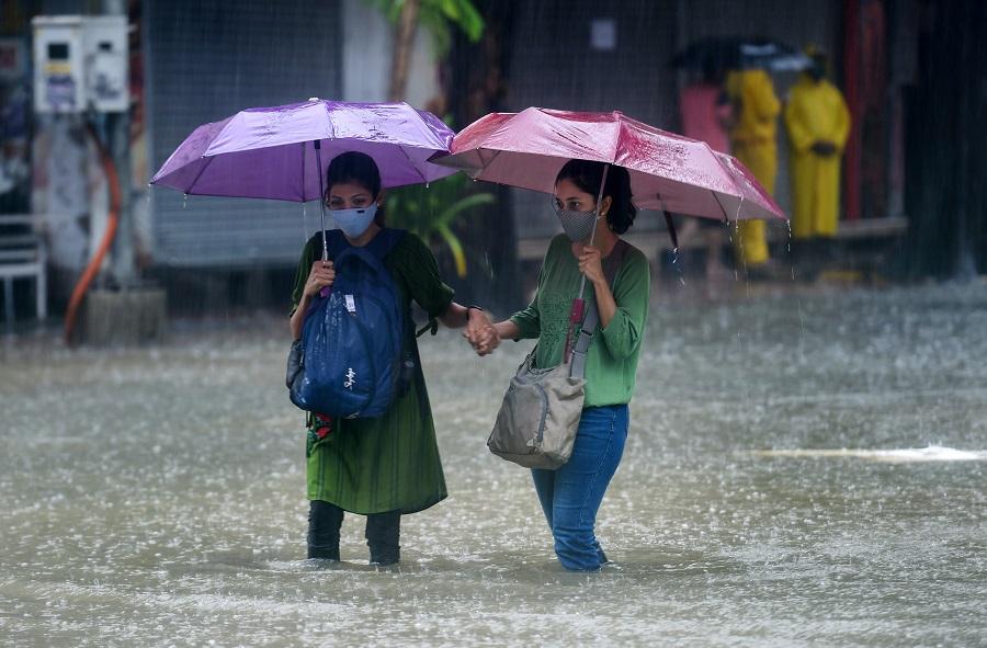 People wade through a waterlogged street at Hindmata in Mumbai on Wednesday.
