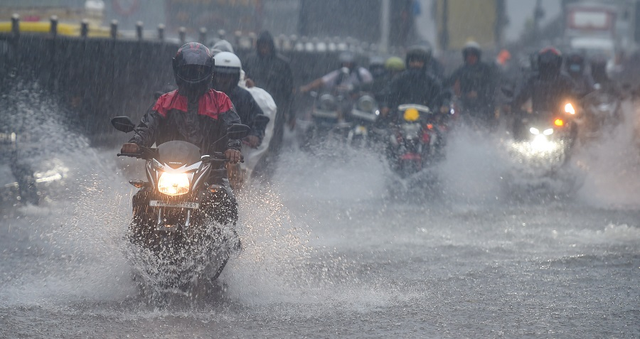 Commuters make their way through the waterlogged road during heavy rain, at Kings Circle, in Mumbai on Wednesday.