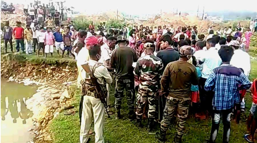 Locals and police gather near the water-filled trench at Birsanagar on Thursday.