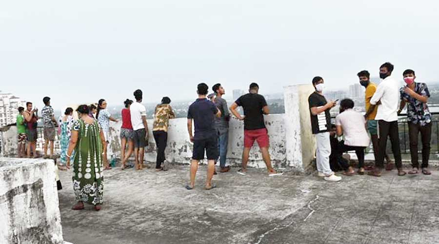Shukhobrishti residents watch from the terrace of a building in the complex after the shootout.