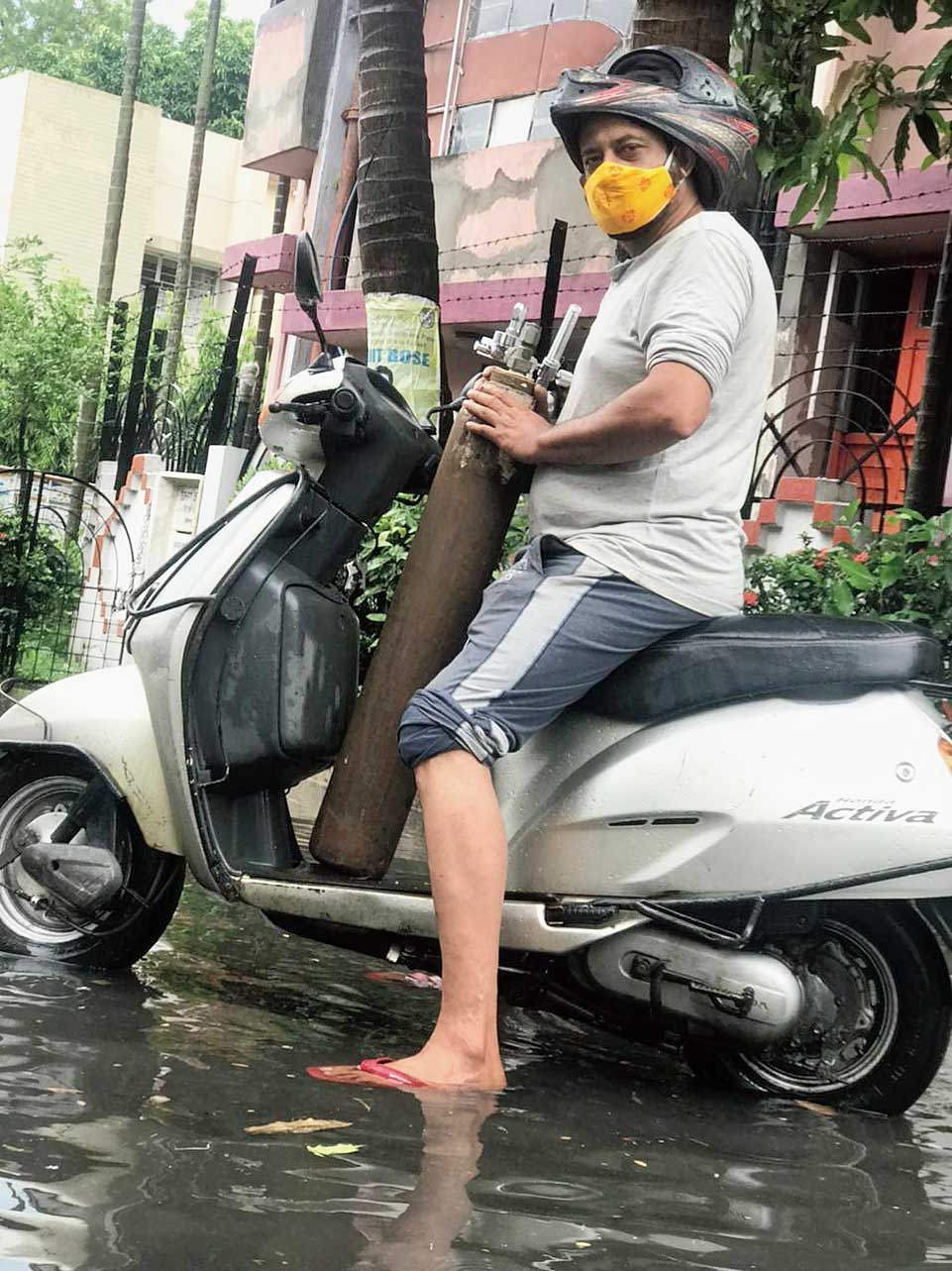 Arijit Mukherjee ferries an oxygen cylinder to a patient on a rainy day