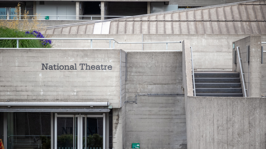 The signage and Brutalist architecture of the National Theatre in the South Bank area, London.
