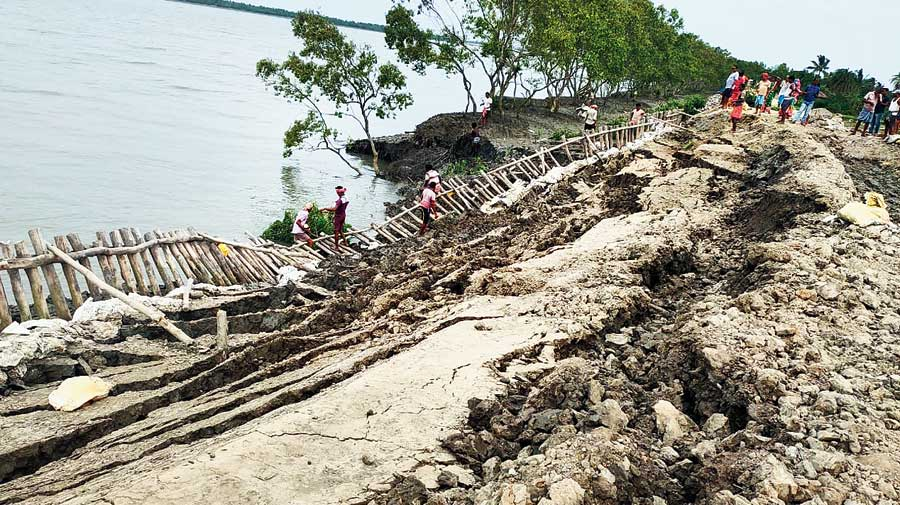 Villagers repair an earthen embankment along the Bidyadhari river in Minakhan on Friday.