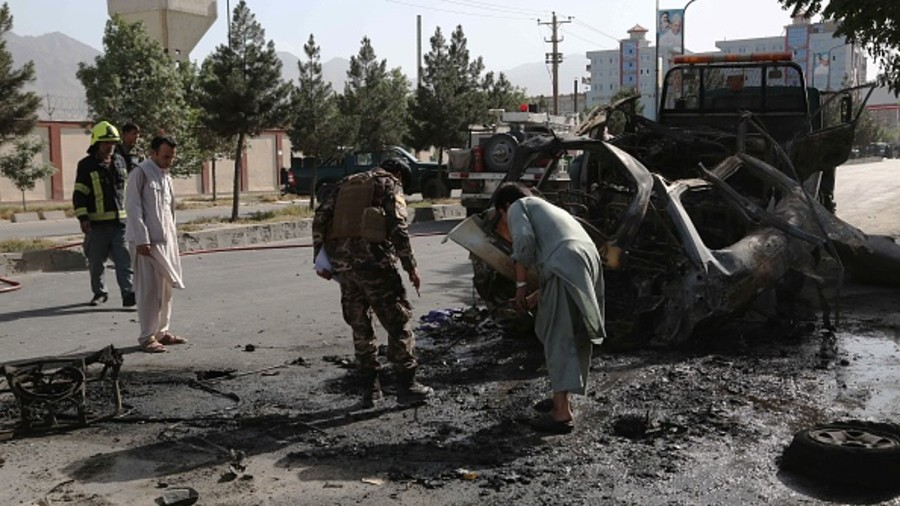 Afghan security forces inspect the remains of a vehicle at the site of a bomb blast in Kabul