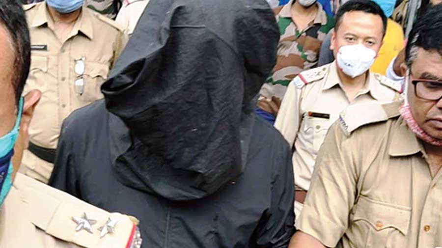 Han Junwei (covered) being taken by the police to court in Malda on Saturday