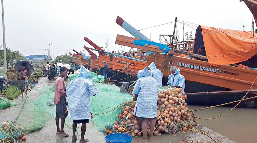 Fishermen with rolled-up nets waiting to be loaded on their vessels at Kakdwip, South  24-Parganas, on Tuesday.