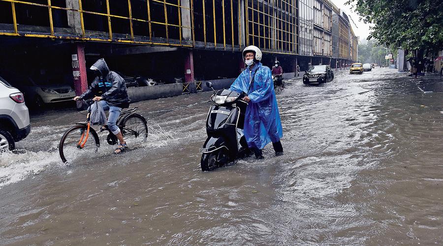 A two-wheeler rider pushes his vehicle through a flooded Rawdon Street on Thursday.