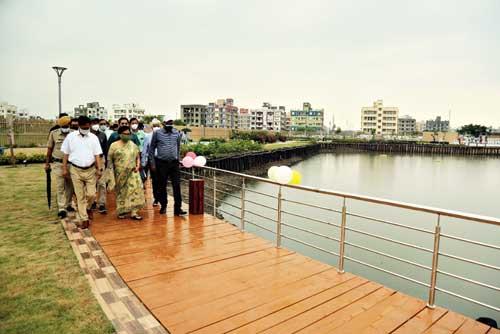 Minister Chandrima Bhattacharya walks up the timber deck flanked by NKDA chairman Debashis Sen and CEO Animesh Bhattacharya