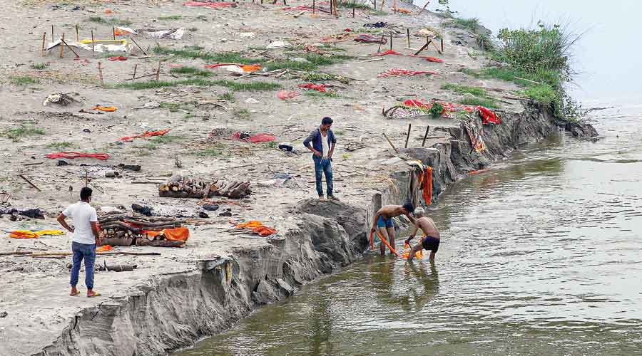 Bodies being shifted from graves on the banks of the Ganga, owing to the threat of soil erosion caused by the increasing water level in the river, at Phaphamau in Allahabad on June 5