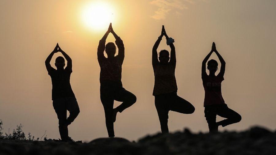 Morning walkers perform Yoga at Mandi village in Jammu on International Yoga Day eve on Sunday.