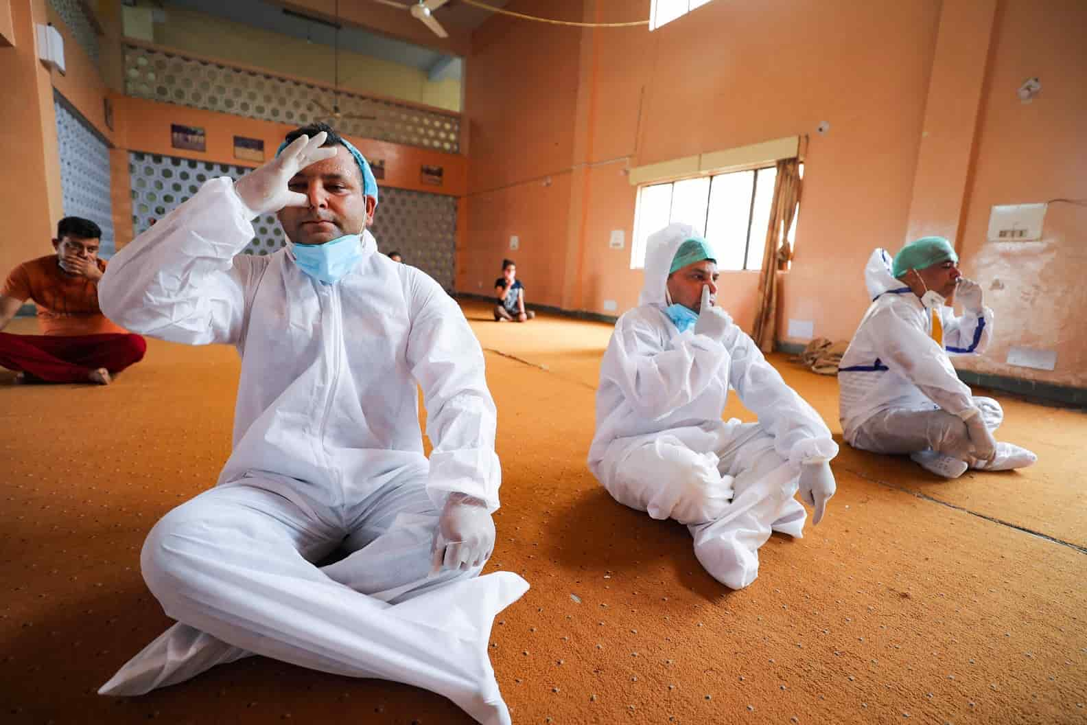 Health workers and patients in PPE engage in Yoga on International Yoga Day eve at a Covid care centre in  Jammu.