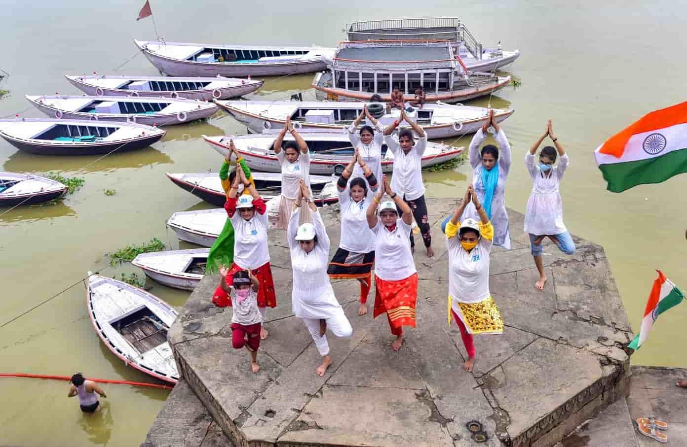 Women and children do asanas at Ganga Ghat in Varanasi on Sunday.