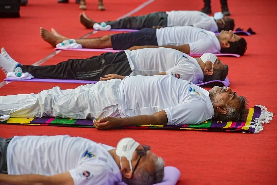 Culture and Tourism Minister Prahlad Singh Patel with others perform Yoga on International Day of Yoga at Red Fort in New Delhi on Monday