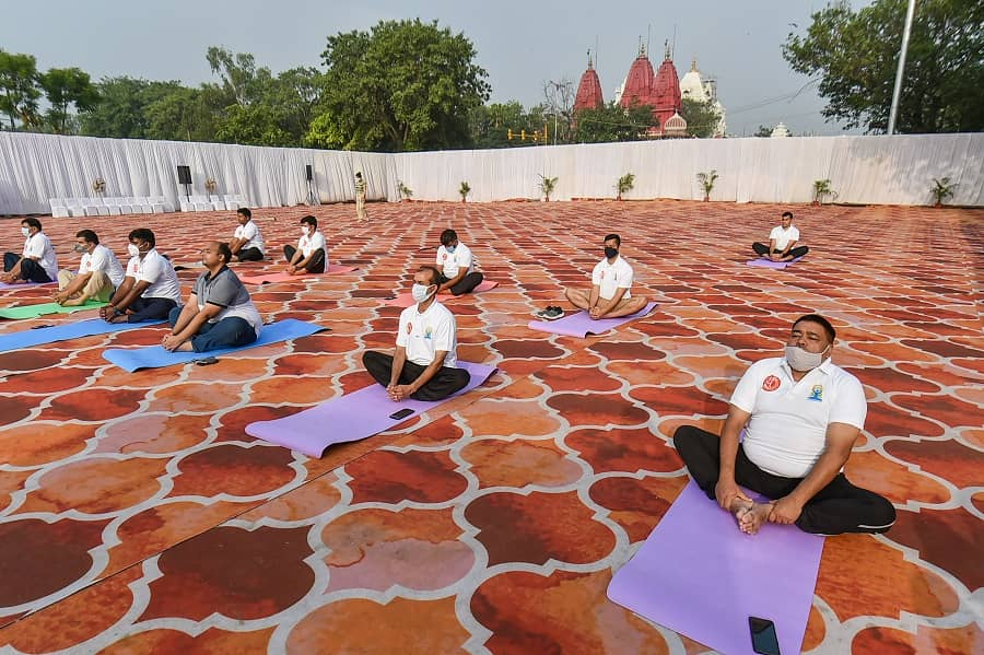 People perform Yoga on International Day of Yoga at Red Fort in New Delhi on Monday.