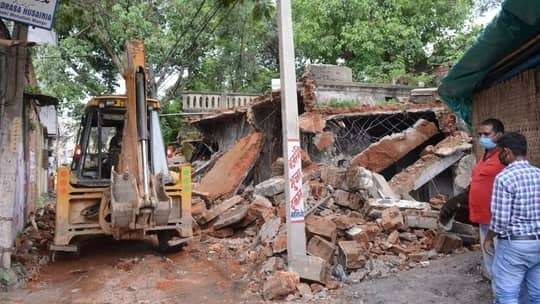 Mango civic authorities use an earthmover to pull down the dilapidated tehsil office at Dimna Road in Jamshedpur on Tuesday.