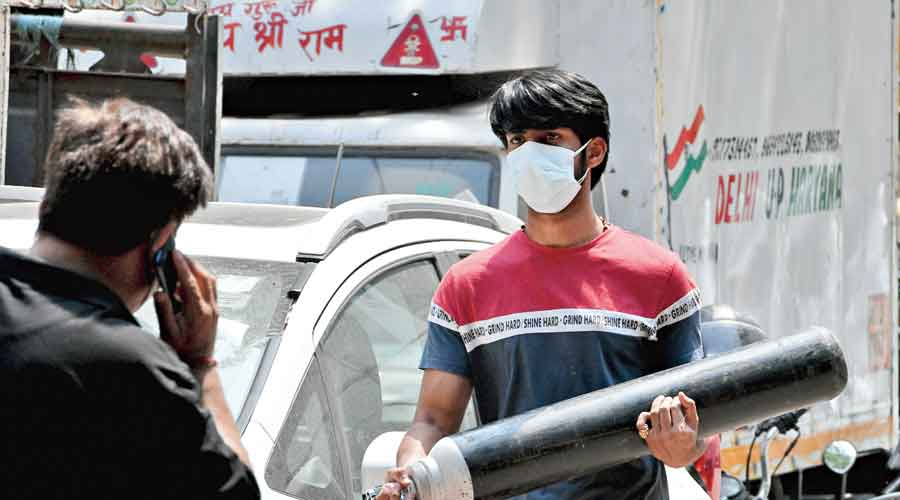 A family member of a Covid-19 patient carries an oxygen cylinder in New Delhi on May 8 after refilling it.