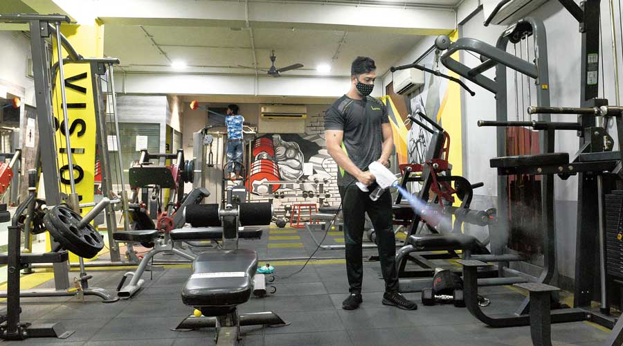 A gym on Raja Basanta Roy Road being sanitised on Tuesday. The state government has allowed gyms to operate with 50 per cent capacity from Thursday.